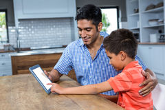 Smiling father using tablet with his son Royalty Free Stock Images