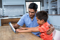 Smiling father using tablet with his son Royalty Free Stock Photo
