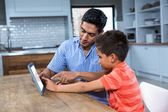 Smiling father using tablet with his son Stock Photo
