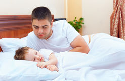 Smiling father watching the son sleeps Royalty Free Stock Image