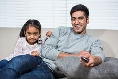 Smiling father watching tv with daughter on the sofa Royalty Free Stock Image