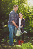Smiling father watering garden with little daughter Stock Photo