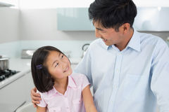Smiling father and young daughter in kitchen Stock Image