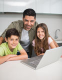 Smiling father with young kids using laptop in kitchen Stock Photo