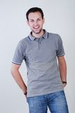 Smiling fellow. Portrait of young fellow dressed in a grey sport shirt and dark blue jeans Stock Photography