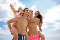Smiling fellows in swimming trunks holding beautiful girls on a seashore on a blurred natural background. Stock Image