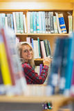 Smiling female amid bookshelves in the library Stock Photos