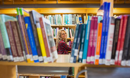 Smiling female amid bookshelves in the library Royalty Free Stock Photography
