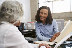 Smiling female analyst in consultation with senior woman stock photo