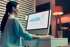 Smiling female analyst creating graphs and diagrams. Working hard. Cheerful pretty woman sitting at the table in her office and creating graphs and diagrams on royalty free stock photography