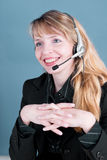 A smiling female answering the telephone. A smiling customer service agent answering the telephone Stock Photo