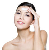 Smiling female applying cosmetic cream on forehead Stock Photo