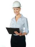 Smiling female architect holding documents Stock Photography
