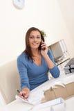 Smiling female architect holding phone and pen Royalty Free Stock Photos