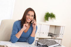 Smiling female architect holding phone and pen Royalty Free Stock Photo