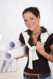 Smiling female architect holding plans and glasses Royalty Free Stock Photos