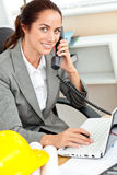 Smiling female architect phoning and using laptop Royalty Free Stock Photos