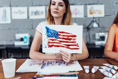 Smiling female artist showing her works, American flag drawn with watercolor technique royalty free stock image