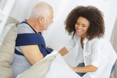 Smiling female assitant with senior man on bed at home royalty free stock photo