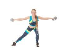 Smiling female athlete exercising with dumbbells Royalty Free Stock Images