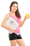 A smiling female athlete holding a weight scale and glass of ora stock images
