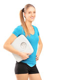 A smiling female athlete holding a weight scale and looking at c Royalty Free Stock Photo