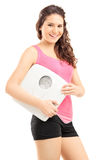 Smiling female athlete holding a weight scale and looking at cam Royalty Free Stock Photo