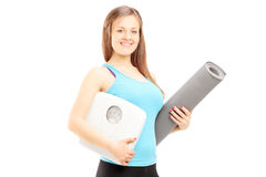 Smiling female athlete holding a weight scale and mat Stock Images