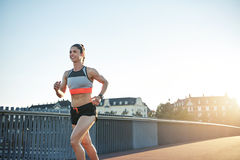 Smiling female athlete running along city bridge Royalty Free Stock Photos