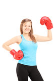 Smiling female athlete wearing red boxing gloves and posing Stock Image