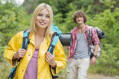 Smiling female backpacker looking away with man standing in background at forest Stock Images