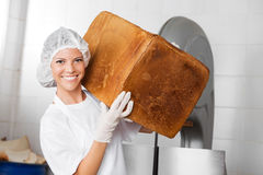 Smiling Female Baker Carrying Big Bread Loaf royalty free stock photo