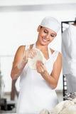 Smiling Female Baker Holding Dough Stock Photo
