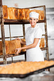 Smiling Female Baker Removing Bread Loaf From Rack Stock Image