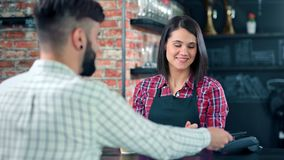 Smiling female barista making fresh fragrance coffee paper cup to male customer at loft cafe. Smiling female barista making fresh fragrance coffee paper cup to stock footage