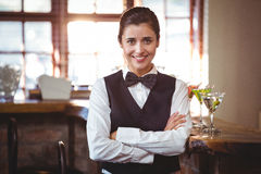 Smiling female bartender standing with arms crossed Stock Photography