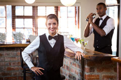 Smiling female bartender standing at bar counter. Portrait of female bartender standing at bar counter Stock Photos