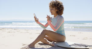 Smiling female on beach using smartphone Royalty Free Stock Image