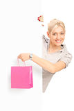 Smiling female behind white panel holding a bag. Smiling young female behind white panel holding a pink bag, isolated on white background Royalty Free Stock Images