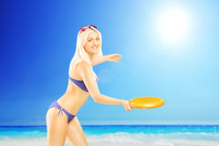 Smiling female in bikini playing with frisbee on a beach. Next to the sea Royalty Free Stock Photo