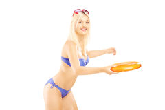 Smiling female in bikini playing with frisbee Stock Photos