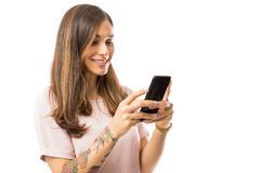 Smiling Female Blogger Text Messaging On Mobile Phone. Against white background royalty free stock photos