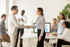 Female boss promoting rewarding handshaking male employee while. Smiling female boss promoting rewarding handshaking motivated worker showing respect while team stock photography