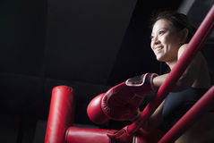 Smiling female boxer resting her elbows on the ring side, looking away, low angle view Stock Photos