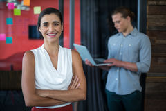 Smiling female business executive standing with arms crossed in office Stock Photos