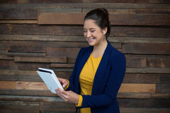 Smiling female business executive using digital tablet. In office Stock Photos