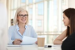 Smiling female businesswoman hold meeting with colleagues in off. Smiling mature businesswoman hold paperwork, discussing project with colleagues at meeting royalty free stock photo