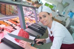 Smiling female butcher cutting meat. Butcher stock photo