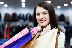 Smiling female buyer with shopping bags. At clothing store Royalty Free Stock Photo