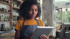 A smiling female cafe owner using digital tablet stock video